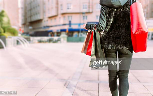 Back view of young woman carrying shopping bags