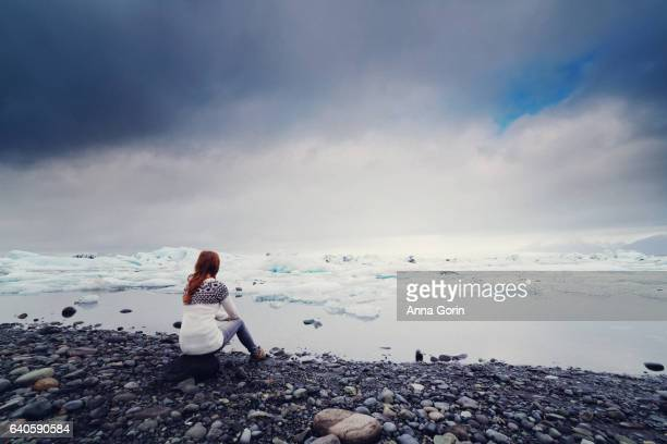 Back view of young woman in sweater sitting at edge of Jokulsarlon glacial lagoon