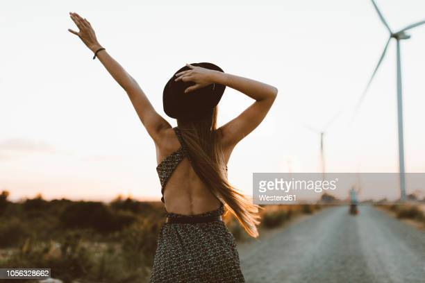 back view of young woman on rural road at sunset - backless stock pictures, royalty-free photos & images