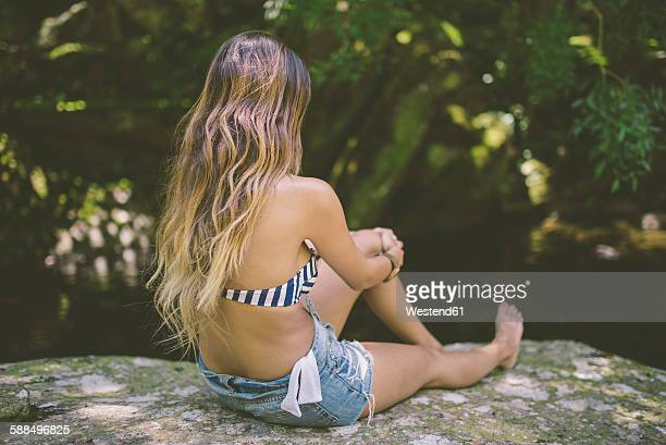 Back view of young woman sitting on a rock near river