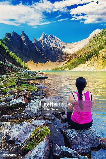 Back view of young woman sitting on rocks by shore of Lake Agnes in Banff National Park, Alberta