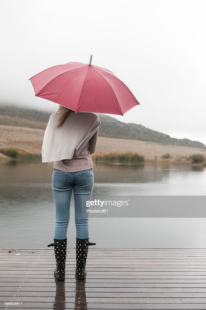 back view of young woman standing in the rain with umbrella ストック