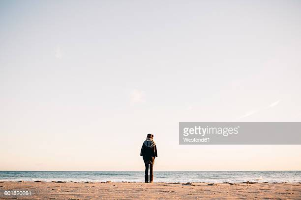 Back view of young woman standing on the beach in winter