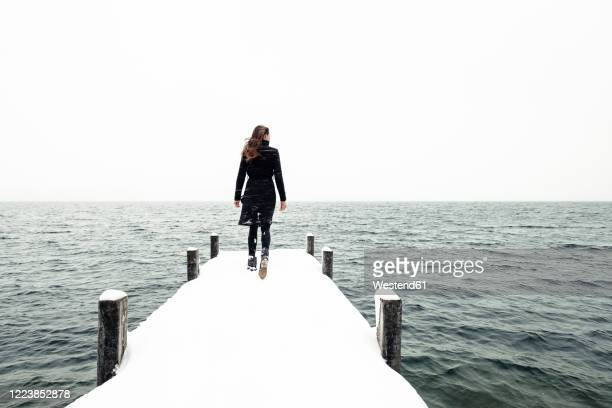 back view of young woman walking on snow-covered jetty at lake starnberg, germany - coat stock pictures, royalty-free photos & images