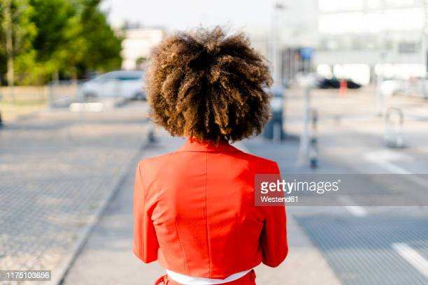 back view of young woman wearing fashionable red suit jacket - red suit stock pictures, royalty-free photos & images