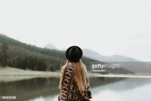 Back view of young woman wearing hat and poncho sitting in front of a lake