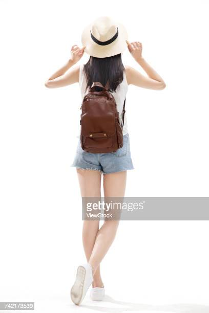 Back view of young woman with backpack