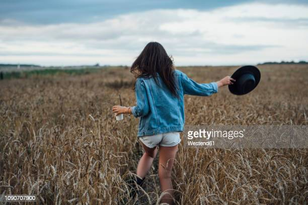 back view of young woman with beverage and hat walking in corn field - mini short photos et images de collection