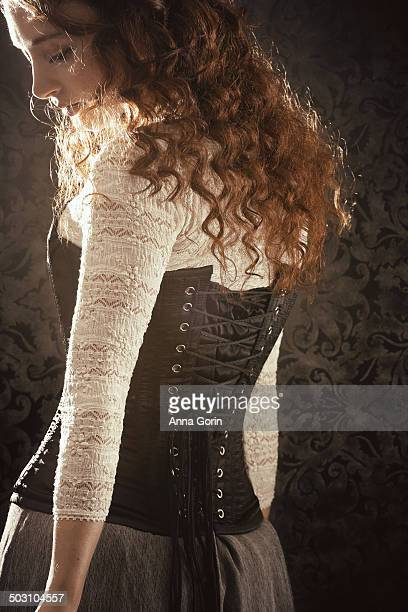 Back view of young woman with curly hair in corset