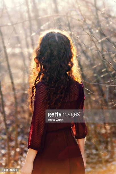 Back view of young woman with long wavy red hair wearing 3/4-sleeve burgundy dress, sunlit in forest