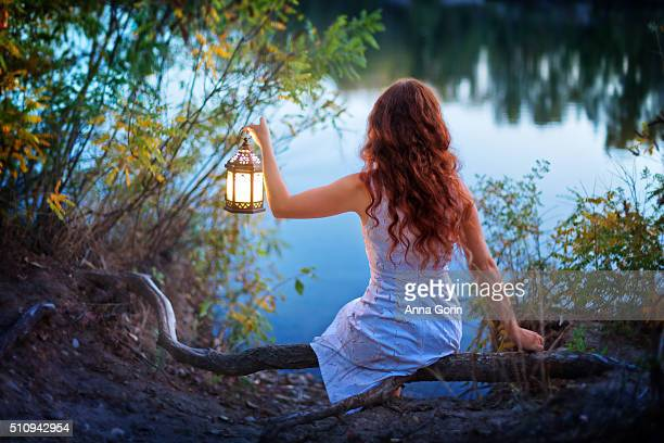 Back view of young woman with long wavy red hair wearing sleeveless white dress holding small lantern, sitting by lake at dusk