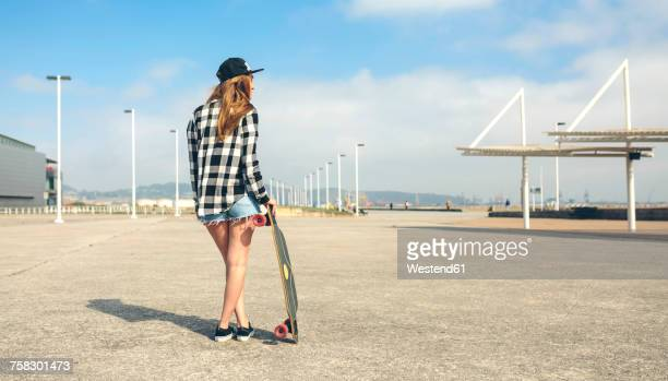 back view of young woman with longboard standing in front of beach promenade, partial view - ホットパンツ ストックフォトと画像