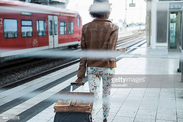 back view of young woman with trolley bag and briefcase at platform - bahnreisender stock-fotos und bilder
