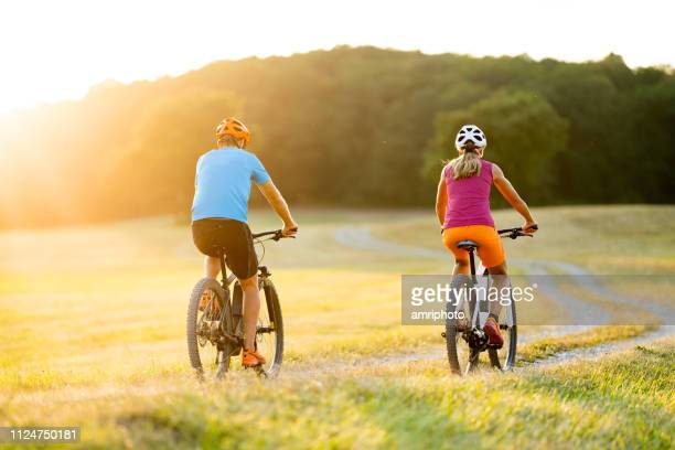 back view two mountain bikers on e bikes in summer sunshine - hybrid vehicle stock pictures, royalty-free photos & images