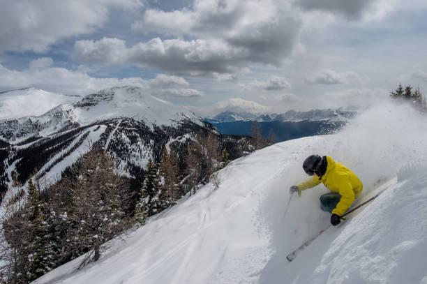 Backcountry skier carves a turn in fresh powder snow