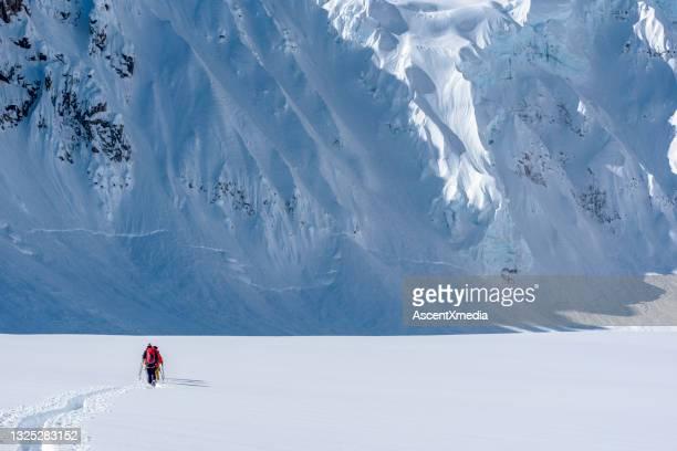sciatore backcountry scala montagne rocciose canadesi innevate - clima alpino foto e immagini stock