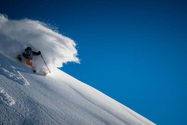 Backcountry skier descends steep powder slope