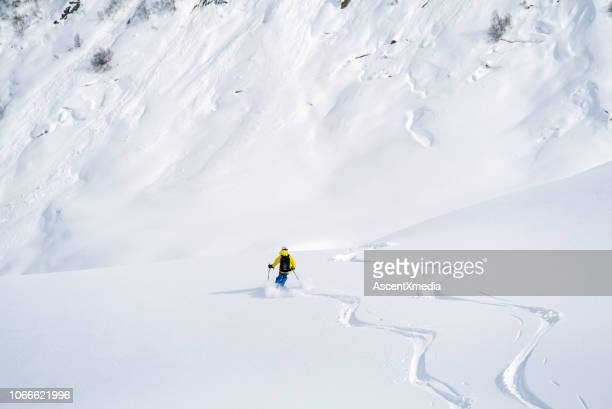 backcountry skier flies down slope - skiing stock pictures, royalty-free photos & images