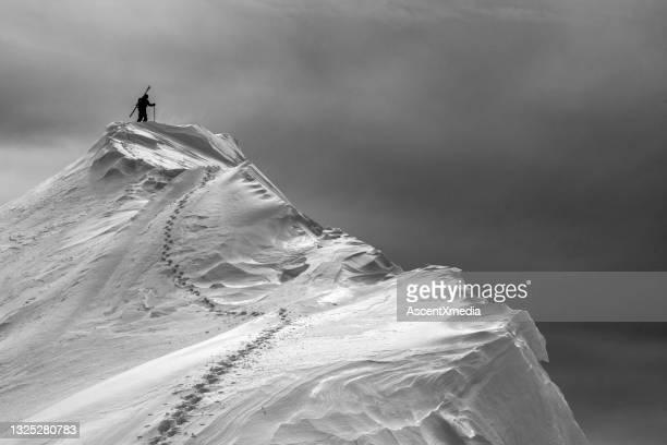 sciatore di backcountry cammina su cima innevata - clima alpino foto e immagini stock