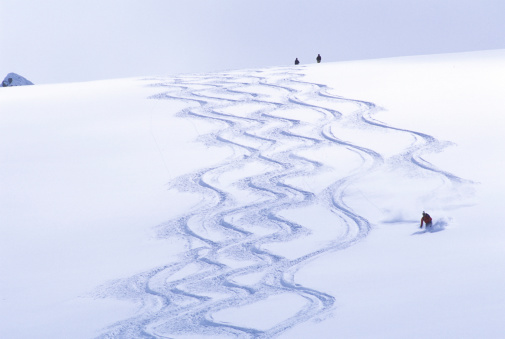 Backcountry skier matching tracks downhill. - gettyimageskorea