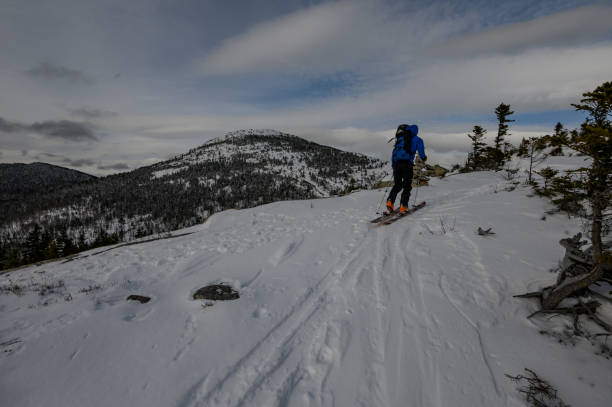 Backcountry skier skinning up a mountain in New Hampshire