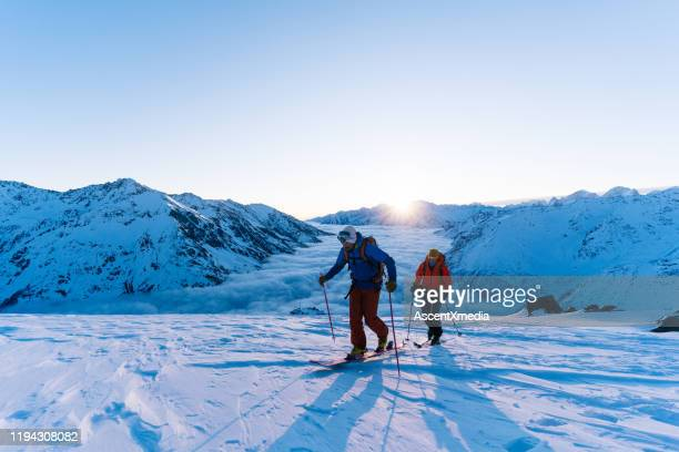 backcountry skiers ascend snowy ridge - moving up stock pictures, royalty-free photos & images