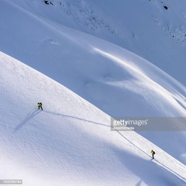 gli sciatori del backcountry scalano le montagne rocciose canadesi innevate - clima alpino foto e immagini stock