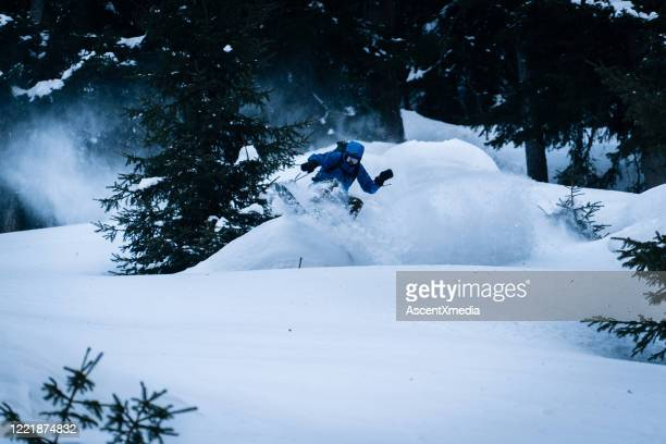 le snowboarder d'arrière-pays descend la montagne - sport d'hiver photos et images de collection