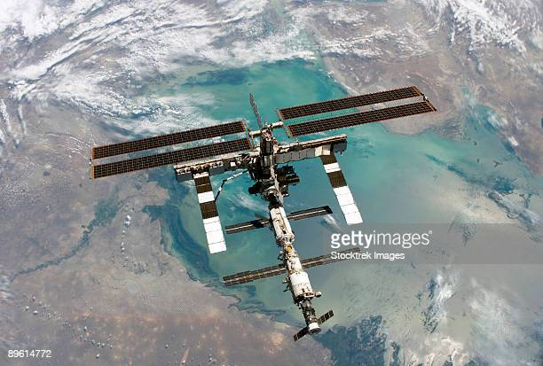 backdropped by a colorful earth, this full view of the international space station was photographed from the space shuttle discovery during the sts-114 return to flight mission, following the undocking of the two spacecraft. - 国際宇宙ステーション ストックフォトと画像