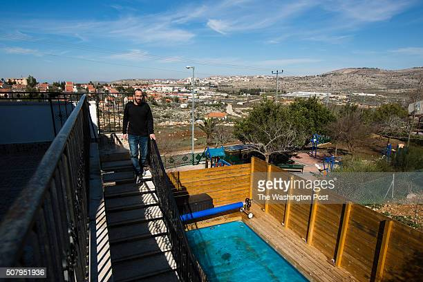 Backdropped by a view of the Jewish settlement of Ofra and the Palestinian village of Silwad Yoav Sorek is seen as he walks down a staircase at his...