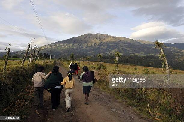 Backdropped by the Galeras volcano a family walks along a road near the shelter El Vergel on the outskirts of Pasto Nariño department Colombia on...