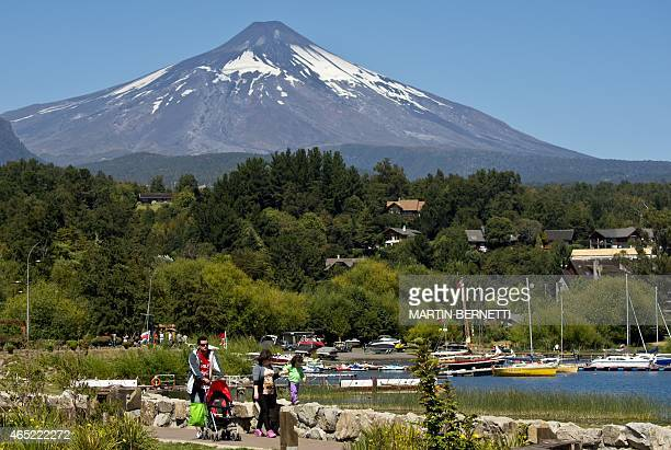 Backdropped by the Villarrica volcano tourists stroll around Pucon in southern Chile on March 4 2015 The Villarrica erupted early Tuesday spewing...