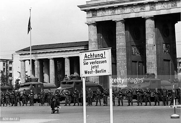 Backed by highpressure water trucks and armored cars East German soldirs bar traffic through the Brandenburg Gate in the center of divided Berlin...