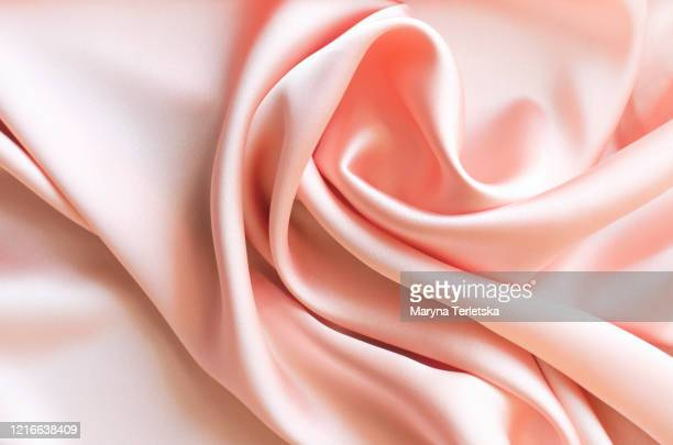 background from satin fabric of peach color. - silk stock pictures, royalty-free photos & images