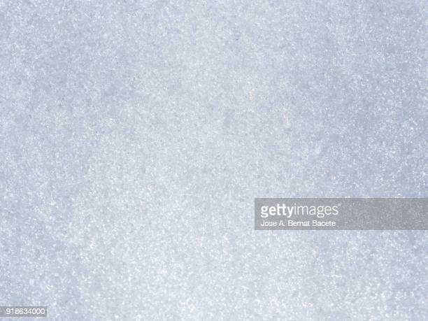 background full frame of snow covered ground illuminated by sunlight. spain - ice stock pictures, royalty-free photos & images