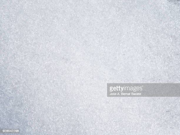 Background Full frame of snow covered ground illuminated by sunlight. Spain