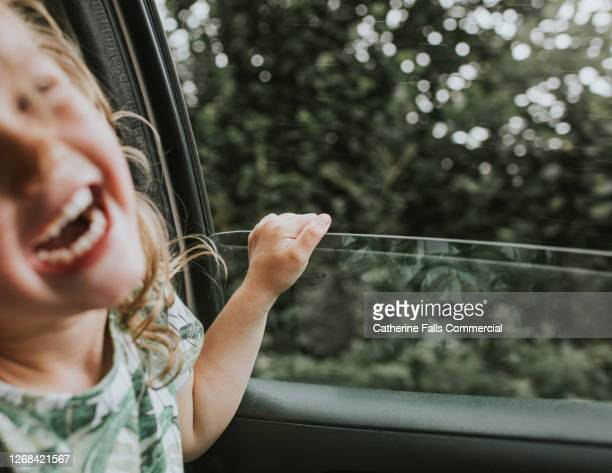 background image of a little girl laughing beside an open car window - humour stock pictures, royalty-free photos & images