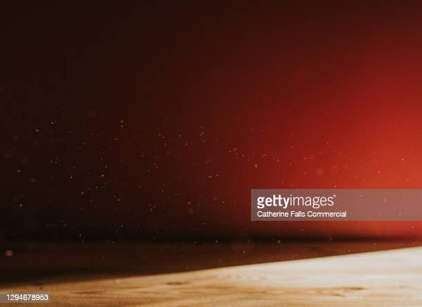 background image of a pink wall behind a wooden table, half in shadow. dust floats, illuminated by sun. - table stock pictures, royalty-free photos & images