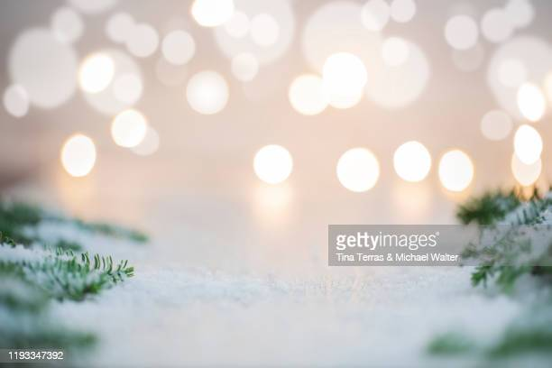 background in christmas mood. bokeh and fairy lights in the background. fir branches and snow. copy space. - focus on background stock pictures, royalty-free photos & images