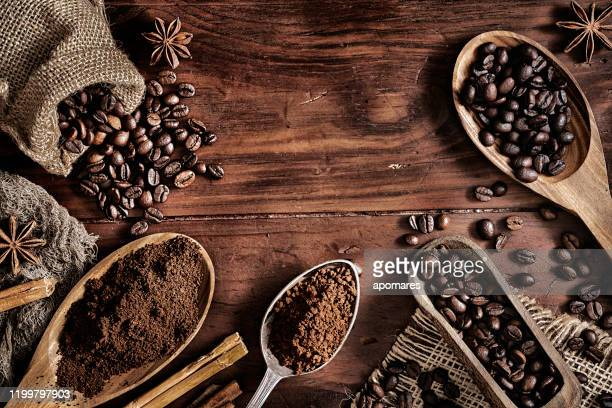 background of coffee beans and grinded coffee on a rustic table - coffee stock pictures, royalty-free photos & images