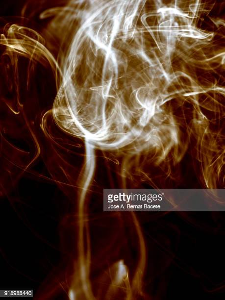 Background of forms and abstract figures of smoke of color gold on a black background.