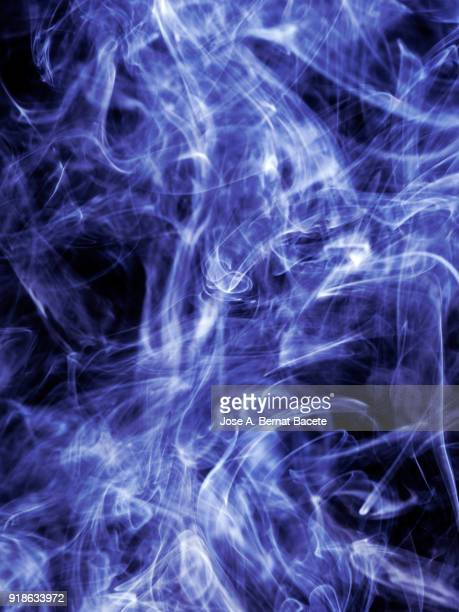 Background of forms and abstract figures of smoke of color light blue on a black background.