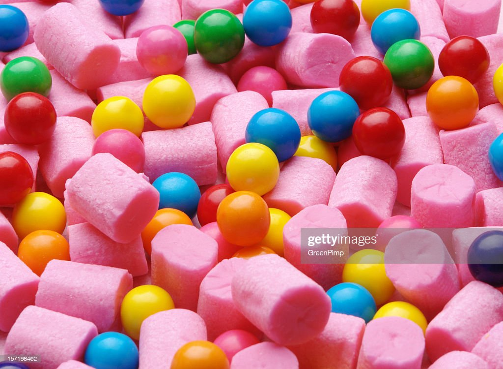 Background of pink cylinder shaped gum and colorful gumballs : Stock Photo