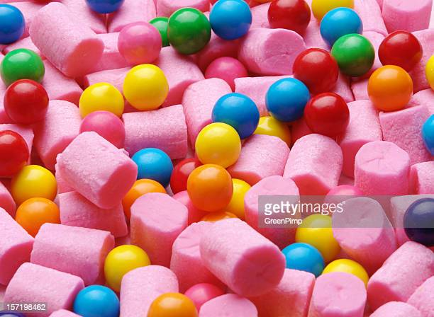 Background of pink cylinder shaped gum and colorful gumballs