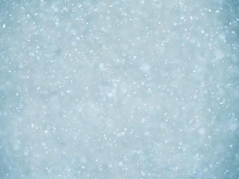 Background of snowflakes of snow that fall down from the sky on a light blue bottom. - gettyimageskorea