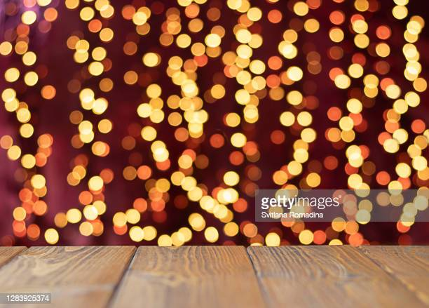 background with wooden table and christmas lights illumination with bokeh - holiday stock pictures, royalty-free photos & images