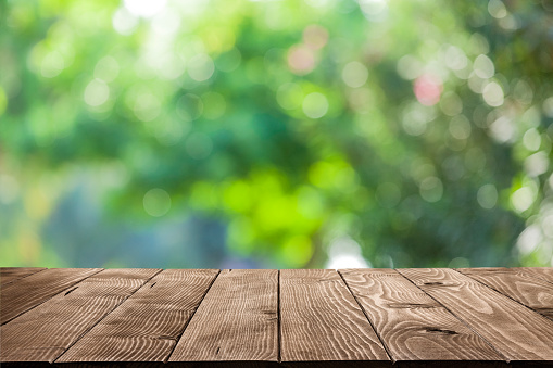 Backgrounds: Empty wooden table with defocused green lush foliage at background 1166687464