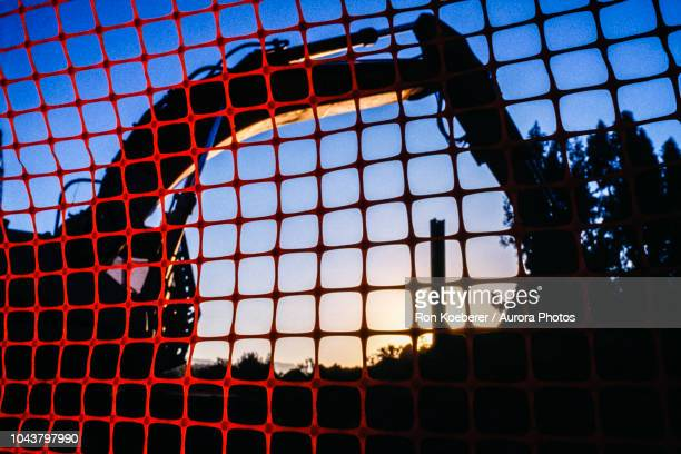 backhoe at construction site seen through temporary red fencing at sunset - koeberer stock pictures, royalty-free photos & images