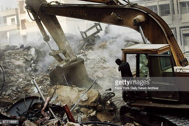 Backhoe is used to remove rubble at a site in southern Beirut, Lebanon, where Israeli bombs leveled nine residential towers on Sunday hours before...