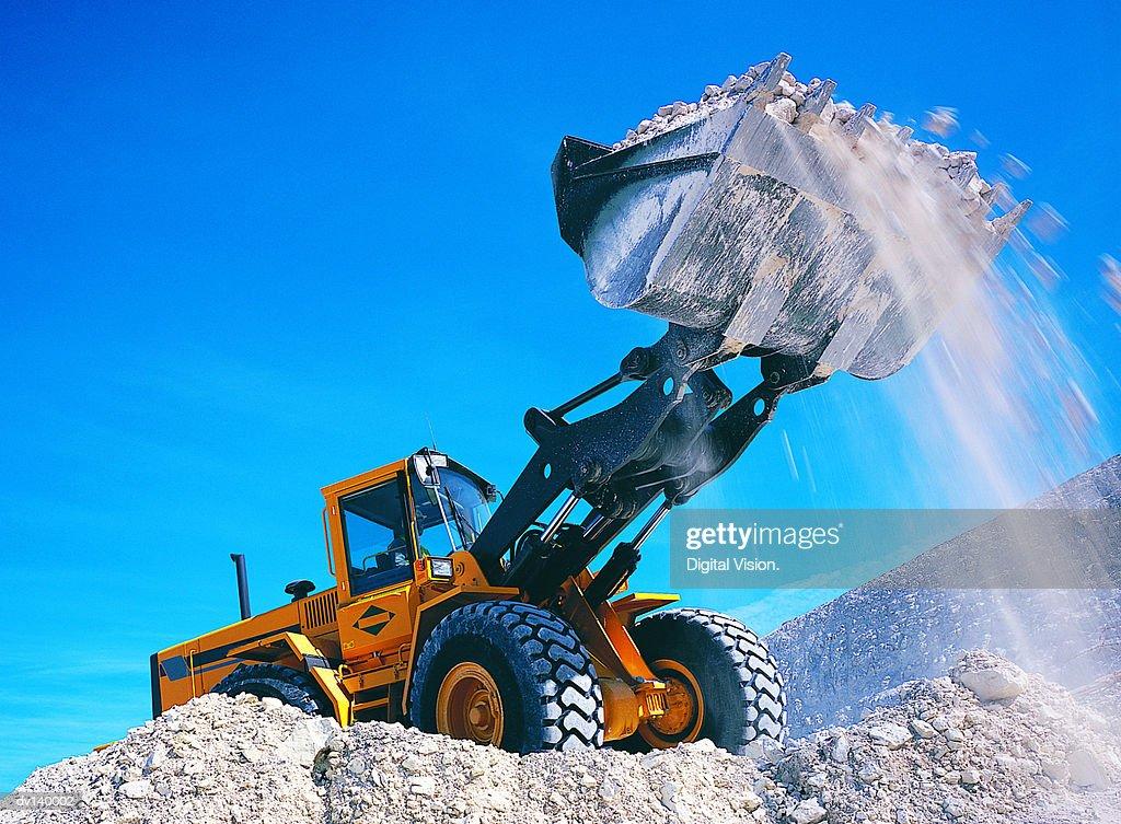 Backhoe lifting rubble : Stock Photo